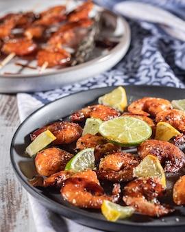 Czarny talerz z domowymi szaszłykami z krewetek smażonych z czosnkiem, cytryną i ziołami, grillowane danie z krewetek, selektywne focus