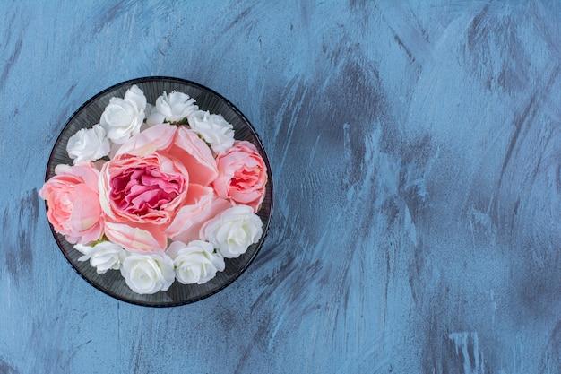 Czarny talerz z fioletowym kwiatem na niebiesko.