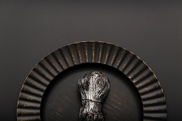 Czarny talerz z makaronem na ciemnym tle