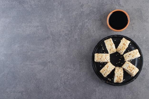 Czarny talerz z pysznymi rolkami sushi z sezamem na tle kamienia.