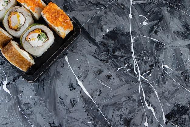 Czarny talerz z różnymi rolkami sushi umieszczonymi na marmurowym tle.