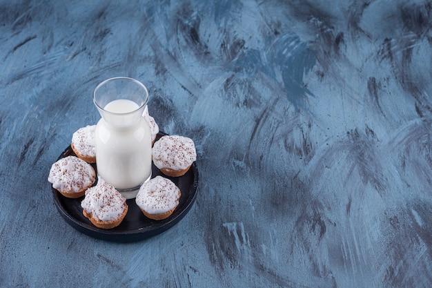Czarny talerz ze słodkimi kremowymi babeczkami i szklanką mleka na marmurze.