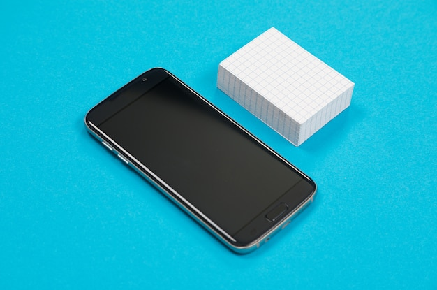 Czarny telefon komórkowy i stos białego zadrapania leżą na lazurowej powierzchni na białym tle