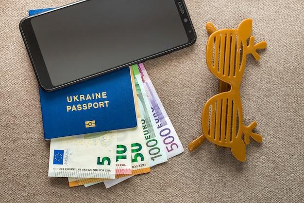 Czarny telefon, pieniądze dolary amerykańskie banknoty rachunki, paszport i zabawki śmieszne okulary na tle przestrzeni kopii, widok z góry. podróże, podróże, planowanie wakacji, przygoda i wanderlust koncepcja.
