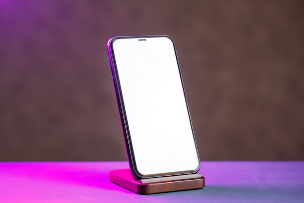 Czarny telefon stoi na drewnianym stojaku. bezprzewodowe ładowanie telefonu