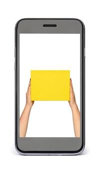 Czarny telefon z białym ekranem i rękami trzymającymi żółte pudełko. koncepcja zakupów online