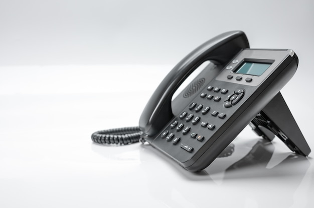 Czarny telefon z wyświetlaczem i przyciskami. nowoczesny telefon do telefonii ip