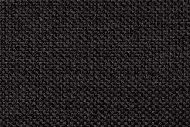 Czarny tło z galonowym w kratkę wzorem, zbliżenie. tekstura tkaniny tkackie, makro