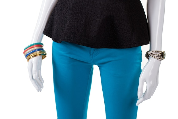 Czarny top i kolorowe bransoletki. kobiecy manekin ubrany w jasną biżuterię. niedrogie akcesoria dla młodych kobiet. towar, który przyciąga uwagę klienta.