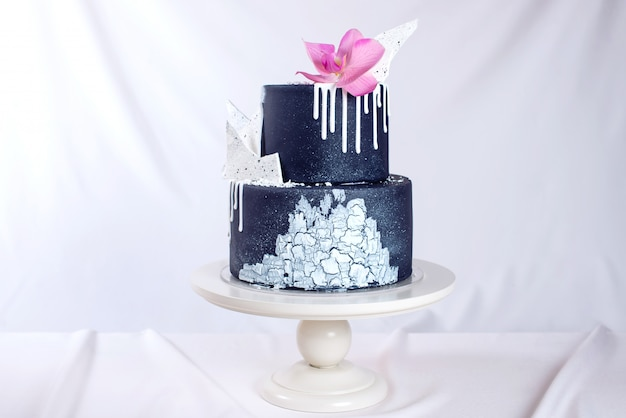 Czarny tort weselny ozdobiony białą czekoladą i kwiatem orchidei