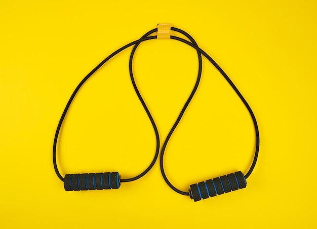 Czarny trener ręki expander na żółtym tle