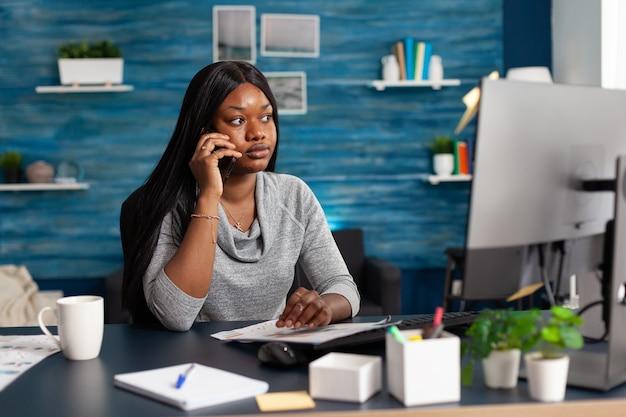 Czarny uczeń siedzący przy biurku w salonie odrabiający pracę domową w liceum