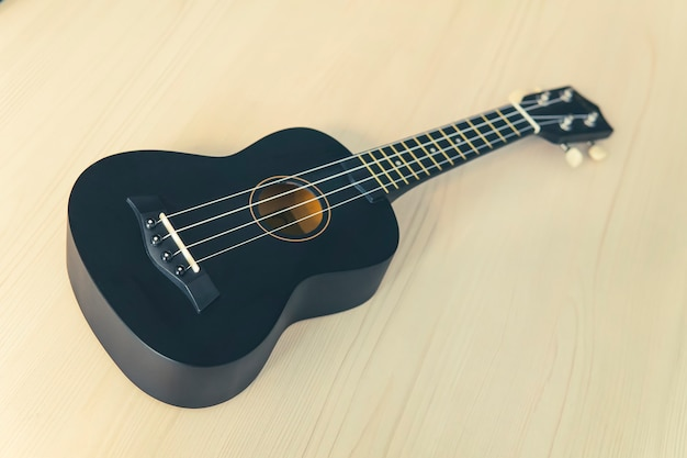 Czarny ukulele na białym tle stół z drewna, puste miejsce. koncepcja muzyki. gitara hawajska