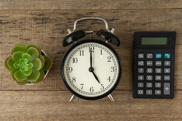 Czarny vintage budzik i kalkulator na drewnianym tle
