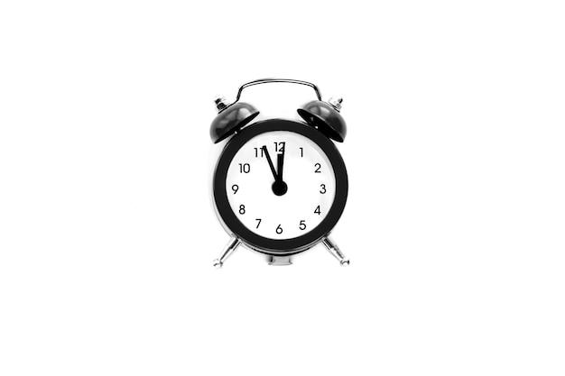 Czarny vintage budzik pokazuje godzinę 12 na białym tle. obudź się i pospiesz się. gorąca wyprzedaż, ostateczna cena, ostatnia szansa. odliczanie do północy nowego roku.