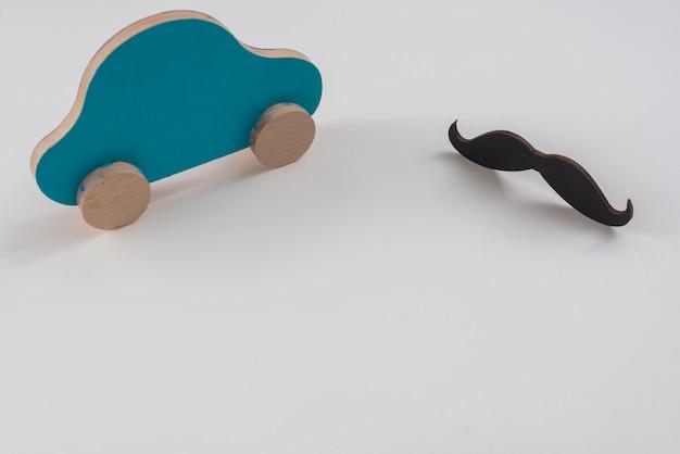 Czarny wąsy z małym samochodem na stole