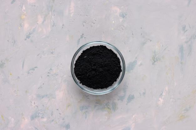 Czarny węgiel aktywny w szklanej misce