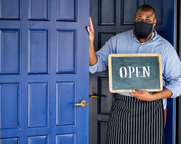 Czarny właściciel firmy w masce podczas nowej normalnej pandemii postu