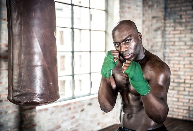 Czarny wojownik ciężko trenuje w swojej siłowni