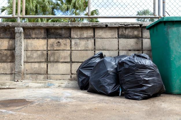 Czarny worek na śmieci ze starą ceglaną ścianą w tle