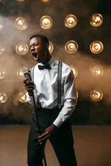 Czarny wykonawca jazzowy śpiewa na scenie. czarny jazzman występuje na scenie z reflektorami