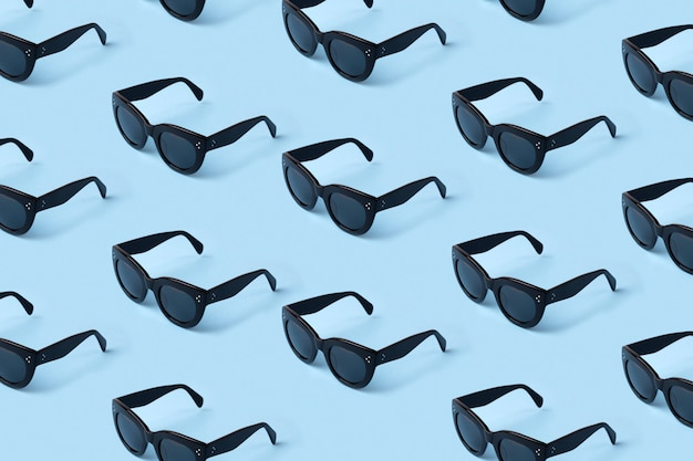 Czarny wzór okularów przeciwsłonecznych na pastelowym niebieskim.