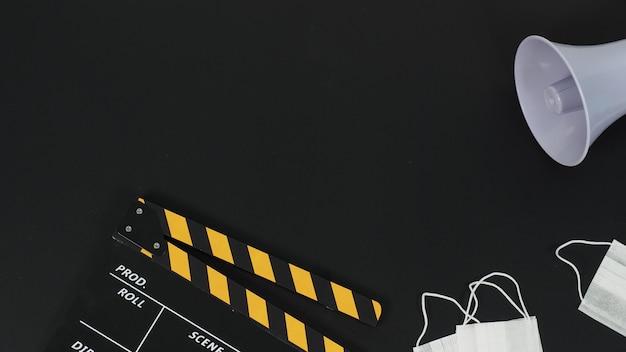Czarny z żółtym klapsem lub klapką filmową i maską, magafon na czarnym tle.