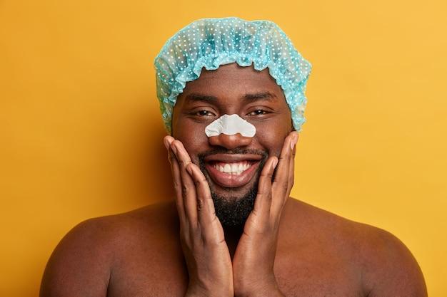 Czarny, zaskoczony brodaty mężczyzna trzyma podbródek, nosi czysty pasek na nosie