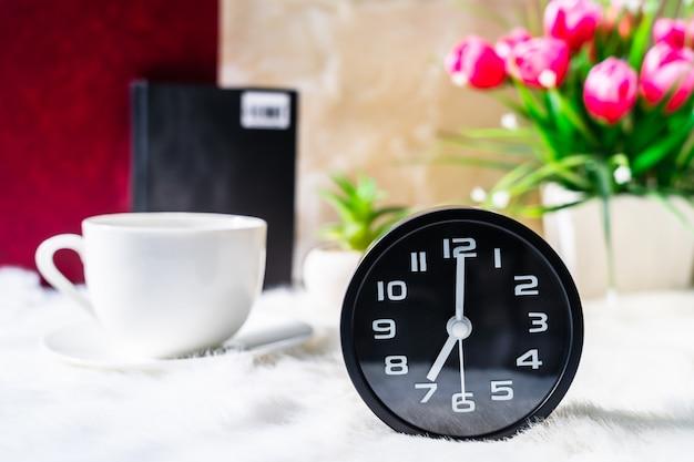 Czarny zegar i filiżanka kawy