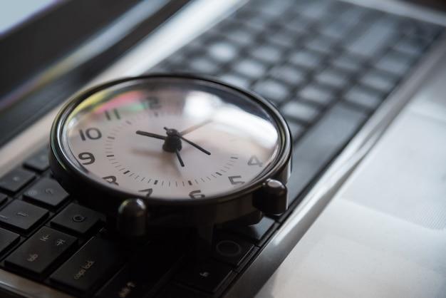 Czarny zegar leżał na klawiaturze koncepcja metafora w ciemny ton niski ton