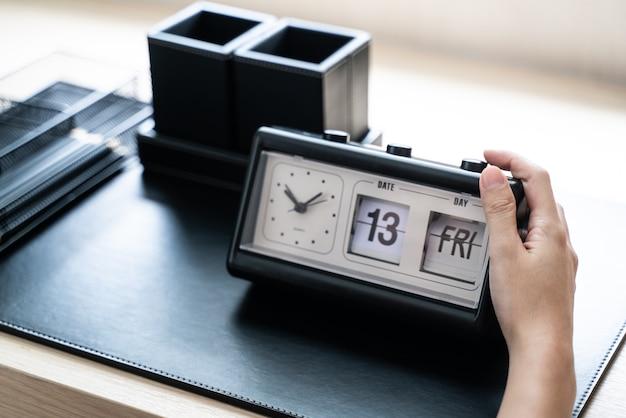 Czarny zegar w ręce na stole roboczym w domu. pokaż datę 13 piątek.