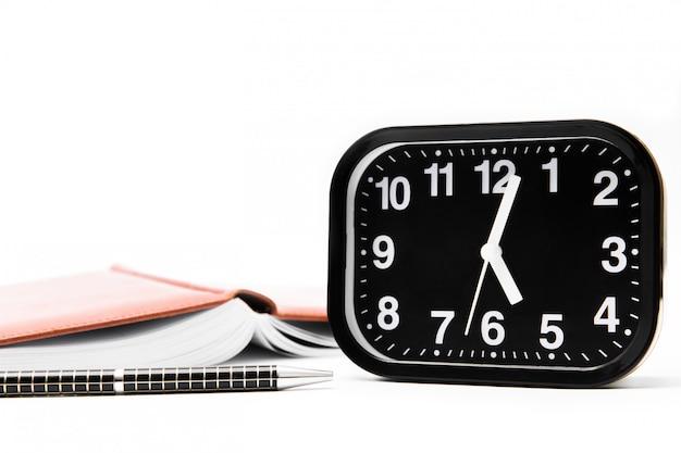 Czarny zegar z piórem i notatnikiem na białym tle. miejsce pracy