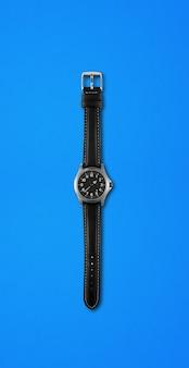 Czarny zegarek na białym tle na niebieskim tle