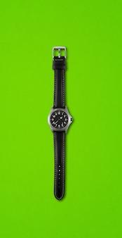 Czarny zegarek na rękę na białym tle na zielonym tle
