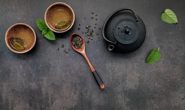 Czarny żeliwny czajniczek z herbatą ziołową ustawiony na ciemnym kamieniu