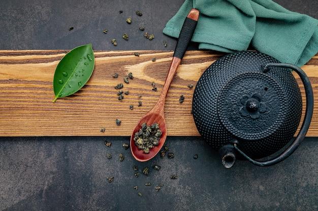 Czarny żeliwny dzbanek do herbaty z herbatą ziołową na ciemnym tle kamienia.