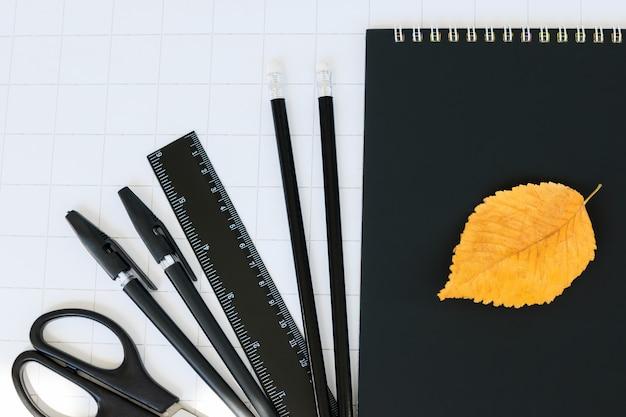 Czarny zestaw papeterii jesienny urlop na białym tle w kratkę powrót do szkoły