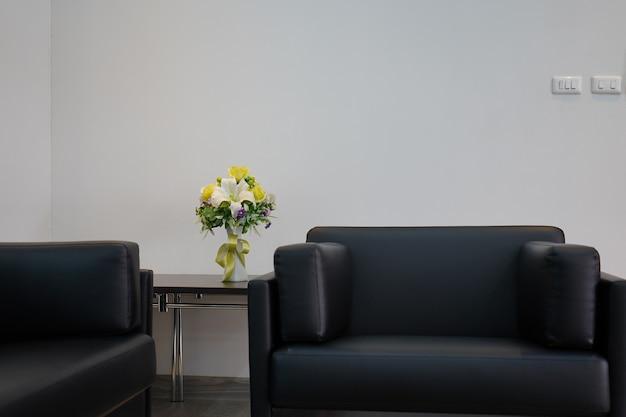 Czarny zestaw sof i żółty wazon z kwiatami ozdobione białą ścianą i miejscem na tekst