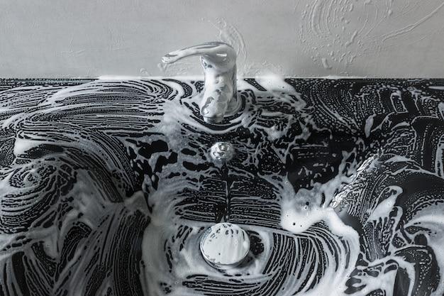 Czarny zlew szklany w piance mydlanej. czyszczenie zlewu. koncepcja - prace domowe, sprzątanie domu.