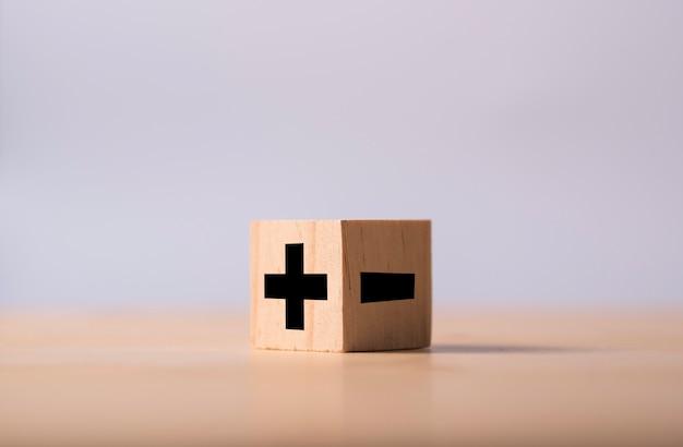Czarny znak plus i minus po przeciwnej stronie drewnianej kostki.