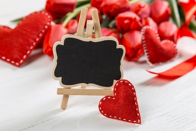 Czarny znak przeciw a czerwoni tulipany na bielu stole. pojęcie dnia matki. skopiuj miejsce