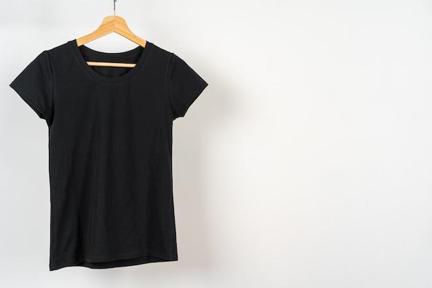 Czarny zwykły t-shirt wisi na wieszaku, miejsce