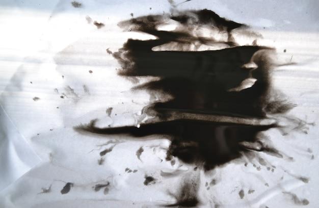 Czarnym atramentem przenoszonym na białym bliska papieru. streszczenie tło na białym tle. plamy z atramentu rozchodzą się i wchłaniają w papierowe makro.
