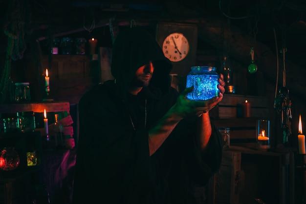 Czarodziej alchemik z butelką magicznej mikstury w rękach w strasznym warsztacie. wiedźmin mag w kostiumie na halloween