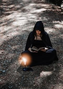 Czarodziejka w przylądku czyta książkę w drewnach