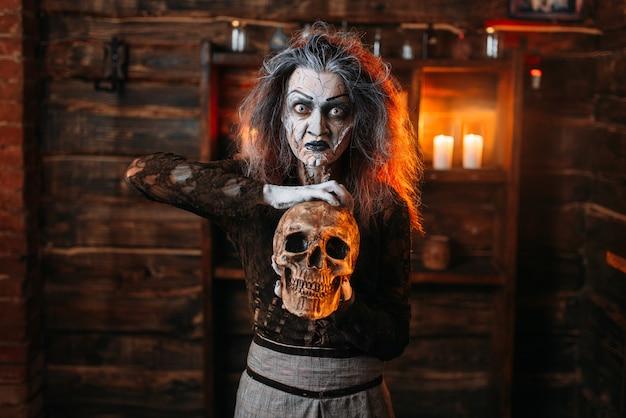 Czarownica czyta zaklęcie, rytuał z ludzką czaszką