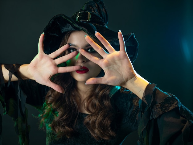 Czarownica tworzy magię młoda piękna brunetka w szpiczastym kapeluszu