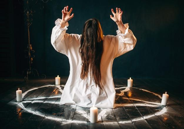 Czarownica w białej koszuli produsuje okultystyczny rytuał w pentagramowym kole ze świecami. rytuał czarnej magii, okultyzm i egzorcyzm