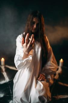 Czarownica w białej koszuli wzywa duchy, pentagram ze świecami, proces rytuału mrocznej magii, czary. okultyzm i egzorcyzm