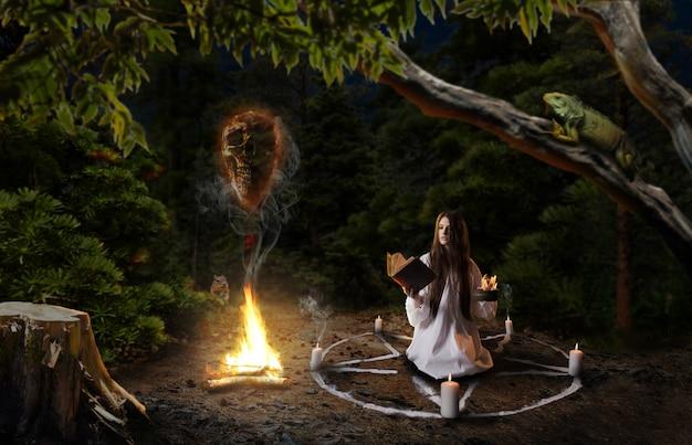 Czarownica w białej koszuli wzywająca duchy zmarłych, koło pentagramowe ze świecami, rytuał mrocznej magii w lesie, czary. okultyzm i egzorcyzm